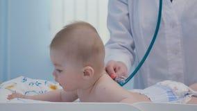 Cuide el examen de las manos del ` s el cuerpo del niño con el estetoscopio metrajes