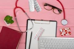 Cuide el lugar de trabajo con el tablero en blanco, el estetoscopio de la medicina, el teclado de ordenador, las lentes, el libro fotos de archivo