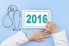 Cuide el número conmovedor 2016 de la mano en la tableta Imagen de archivo