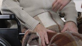 Cuide el recubrimiento del paciente femenino discapacitado mayor en silla de ruedas con la tela escocesa, cuidado metrajes