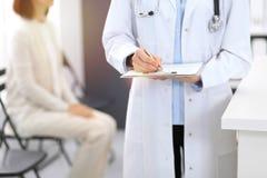 Cuide el relleno de la mujer encima del formulario médico mientras que se coloca cerca del mostrador de recepción en la clínica o imagen de archivo libre de regalías