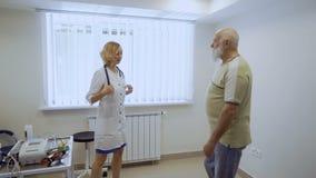 Cuide el saludo con el hombre mayor en el gabinete en clínica almacen de metraje de vídeo