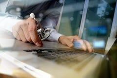 Cuide el trabajo con el ordenador portátil en oficina médica del espacio de trabajo Imagen de archivo libre de regalías