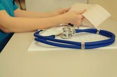 Cuide el trabajo en el hospital que escribe una prescripción, una atención sanitaria y un concepto médico, resultados de la prueb Foto de archivo