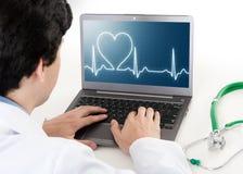 Cuide el trabajo en el ordenador portátil con el ekg del ritmo del corazón en la pantalla Fotos de archivo