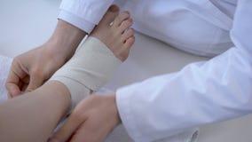 Cuide el vendaje del tobillo torcido, lesión corriente después del entrenamiento, primer de la pierna metrajes