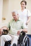 Cuide empujar al hombre en sillón de ruedas Fotos de archivo libres de regalías