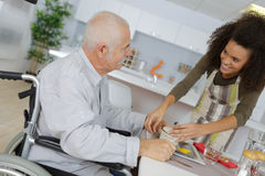 Cuide en el hogar de vieja gente que da la cena paciente imagenes de archivo
