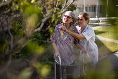 Cuide hablar con la mujer mayor mientras que le ayuda en caminar Fotos de archivo