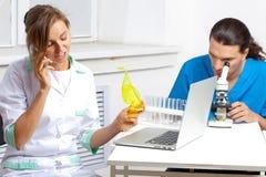 Cuide hablar en un teléfono móvil en laboratorio Imagen de archivo libre de regalías