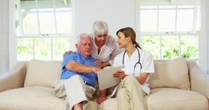 Cuide hacer una revisión médica para arriba con el hombre maduro en un sofá almacen de video