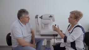 Cuide la charla con el paciente después de comprobar su vista en el equipo moderno almacen de metraje de vídeo