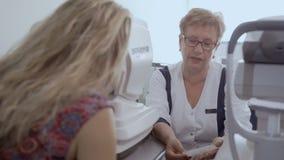 Cuide la charla con la mujer joven después de cheking su vista almacen de metraje de vídeo