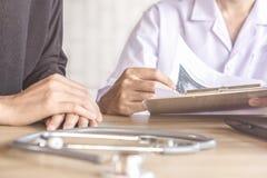 Cuide la cita con el paciente femenino que discute sobre el examen en un hospital foto de archivo libre de regalías