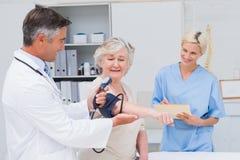Cuide la comprobación de la presión arterial de los pacientes mientras que enfermera que la observa Imagen de archivo libre de regalías
