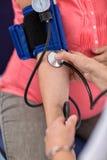 Cuide la comprobación de la presión arterial de una mujer embarazada Imagen de archivo libre de regalías