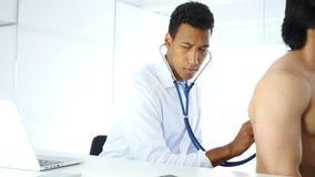 Cuide la comprobación de los pulmones con el estetoscopio, examinando la salud del paciente imagen de archivo