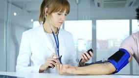 Cuide la comprobación de la presión arterial del paciente en clínica almacen de metraje de vídeo