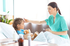 Cuide la comprobación de temperatura de la niña enferma en cama de hospital Imágenes de archivo libres de regalías