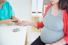 Cuide la comprobación del azúcar de sangre del ` s de la mujer embarazada Fotos de archivo