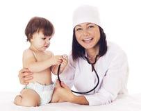 Cuide la comprobación del bebé con el estetoscopio en el fondo blanco Imagenes de archivo