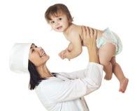 Cuide la comprobación del bebé con el estetoscopio en el fondo blanco Foto de archivo