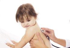 Cuide la comprobación del bebé con el estetoscopio en el fondo blanco Fotografía de archivo