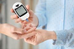 Cuide la comprobación del nivel de azúcar de sangre paciente diabético del ` s fotografía de archivo libre de regalías