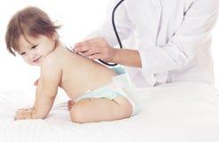 Cuide la comprobación del bebé con el estetoscopio en el fondo blanco. Imagen de archivo