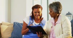 Cuide la explicación de la medicación en el tablero a la mujer mayor en la sala de estar 4k metrajes