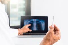 Cuide la explicación de la radiografía de los pulmones en la pantalla de ordenador al paciente fotos de archivo