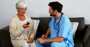 Cuide la explicación de una botella de píldoras al paciente mayor almacen de metraje de vídeo