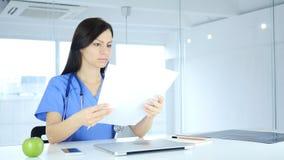 Cuide la lectura de los informes médicos del paciente, sentándose en frente imagen de archivo
