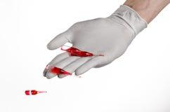Cuide la mano que sostiene un frasco, rojo de la ampolla, ampolla vaccínea, vacuna de Ebola, tratamiento de la gripe, fondo blanc Foto de archivo