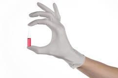 Cuide la mano que sostiene un frasco, rojo de la ampolla, ampolla vaccínea, vacuna de Ebola, tratamiento de la gripe, fondo blanc Imagen de archivo libre de regalías