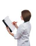 Cuide a la muchacha que se coloca oblicua y escribe en la tableta Fotografía de archivo
