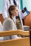 Cuide a la mujer embarazada triste cercana derecha que se sienta en cama de hospital Imagen de archivo libre de regalías