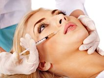 Cuide a la mujer que da inyecciones del botox. Imagen de archivo