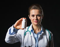 Cuide a la mujer que muestra la botella de la medicina en fondo negro Imagenes de archivo