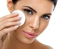 Cuide a la mujer que quita maquillaje de la cara con el cojín de algodón Imagen de archivo