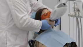 Cuide la preparación de una mujer joven hermosa para el laser que blanquea procedimiento de los dientes almacen de video