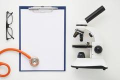 Cuide la tabla con el microscopio, el estetoscopio y los vidrios, visión superior Imagenes de archivo