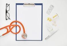 Cuide la tabla con las medicinas, el estetoscopio y los vidrios, visión superior Imagen de archivo libre de regalías