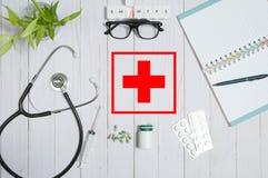 Cuide la tabla con los artículos, el estetoscopio y las píldoras médicos Imagenes de archivo