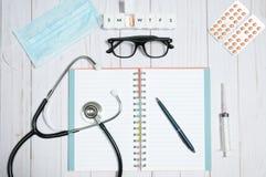 Cuide la tabla con los artículos, el estetoscopio y las píldoras médicos Imagen de archivo