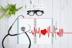 Cuide la tabla con los artículos, el estetoscopio y las píldoras médicos Foto de archivo