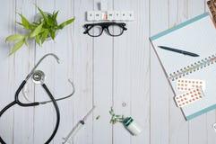 Cuide la tabla con los artículos, el estetoscopio y las píldoras médicos Fotografía de archivo