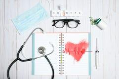 Cuide la tabla con los artículos, el estetoscopio y las píldoras médicos Fotos de archivo libres de regalías
