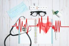 Cuide la tabla con los artículos, el estetoscopio y las píldoras médicos Imagen de archivo libre de regalías