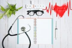 Cuide la tabla con los artículos, el estetoscopio y las píldoras médicos Foto de archivo libre de regalías